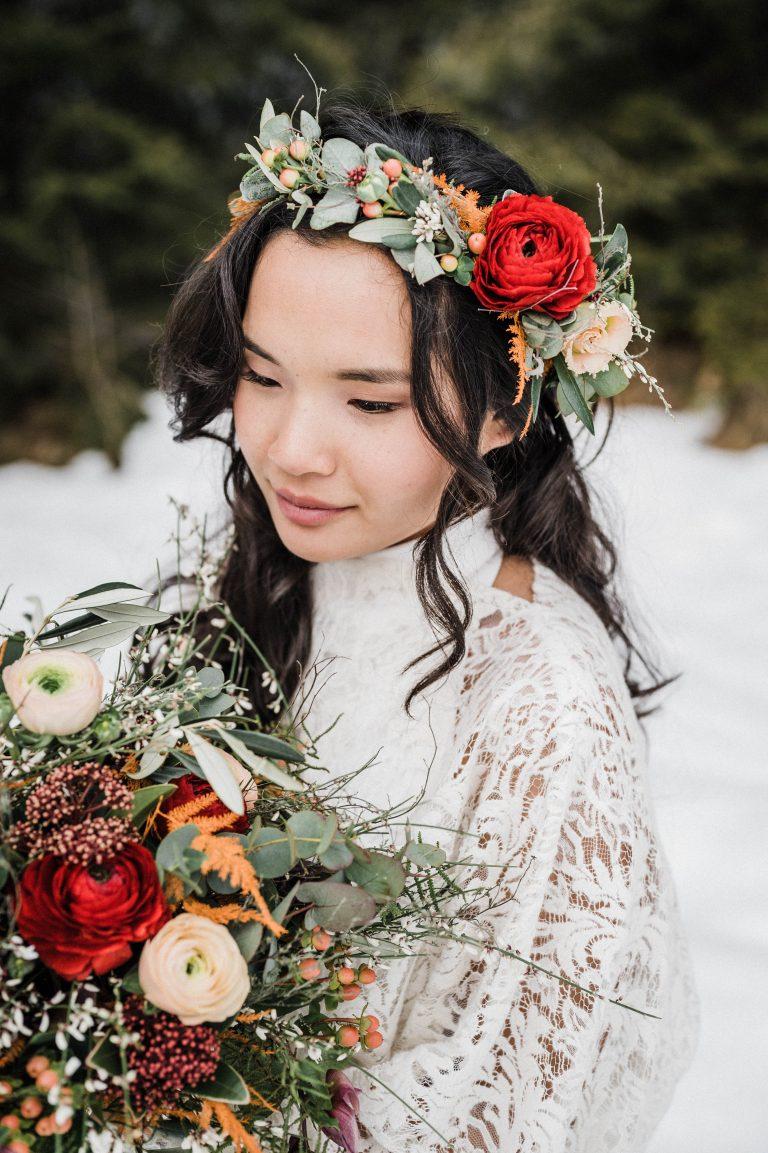 Braut mit Blumenkranz im Haar und passendem Brautstrauß in Winterlandschaft