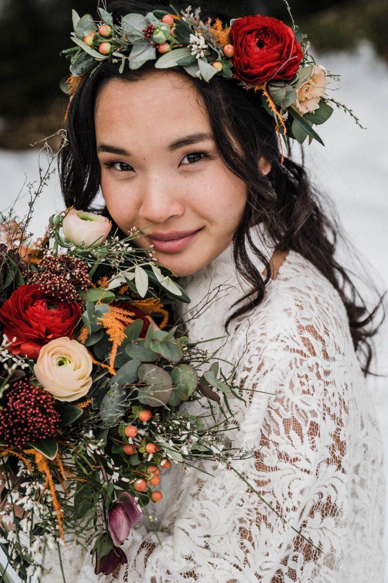 Braut mit Blumen Haarkranz und Brautstrauß im Schnee