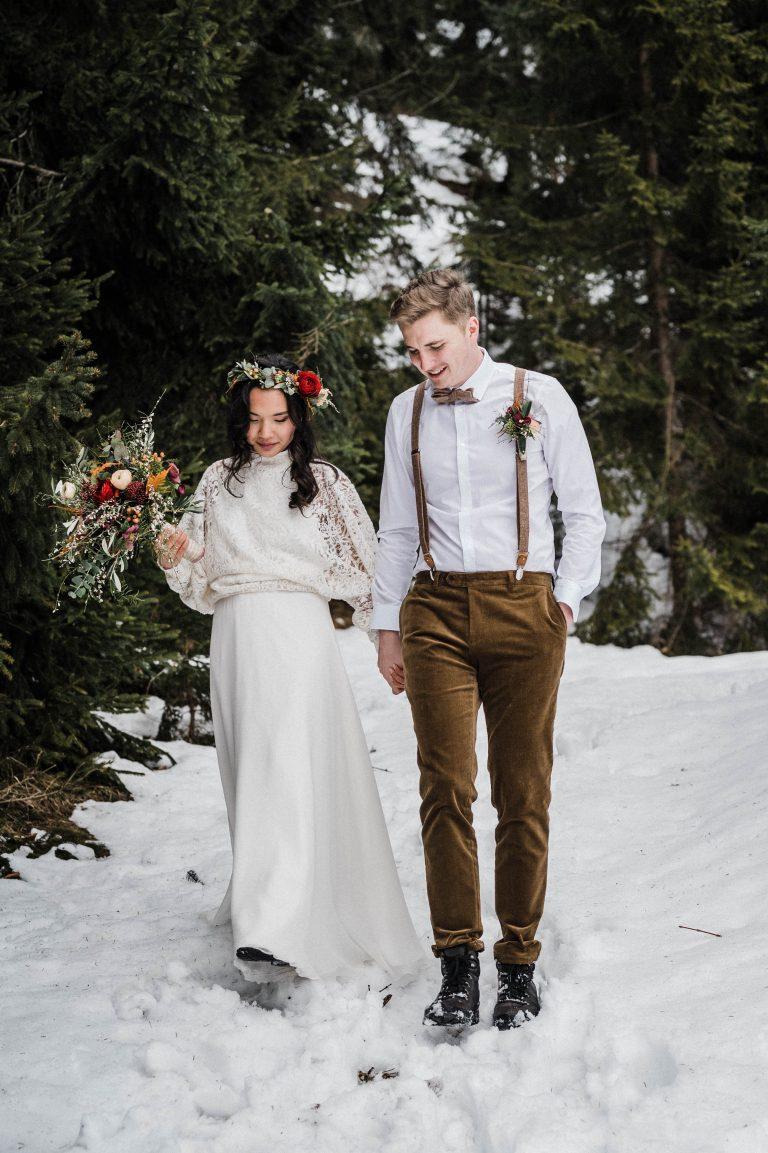 Das Brautpaar schreitet durch den Schnee im Bergwald nach der freien Trauung im Almbad Sillberghaus