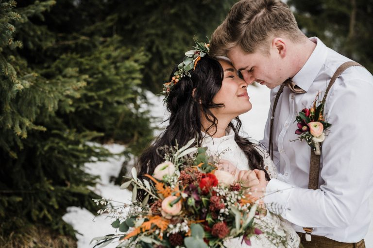 Braut und Bräutigam Stirn an Stirn in Winterlandschaft