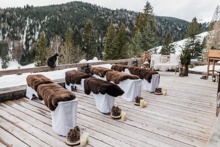 Gastbänke mit wärmenden Fellen, im Hintergrund die Winterlandschaft zur Trauung auf der Terrasse