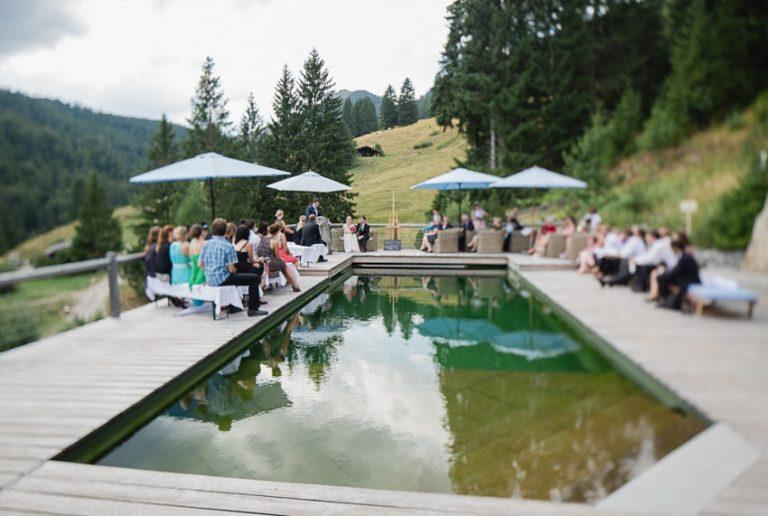 Hochzeitsgesellschaft versammelt zur freien Trauzeremonie am Naturpool des Almbad Sillberghaus
