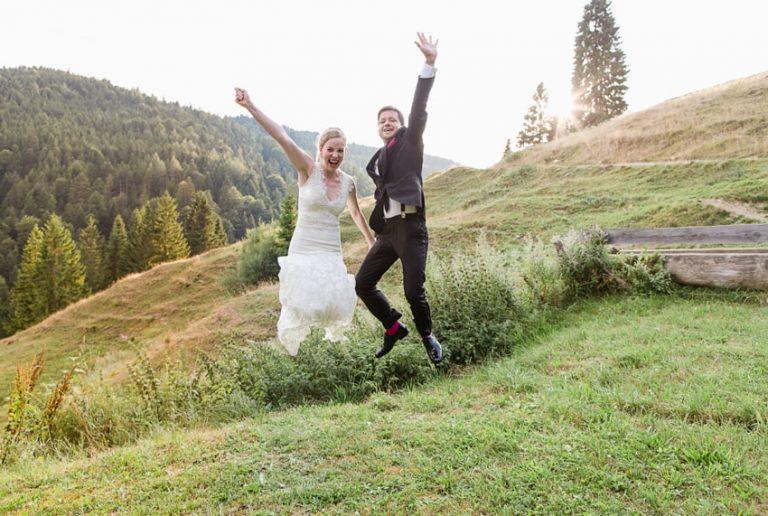 Brautpaar springt jubelnd auf der Almwiese vorm Almbad Sillberghaus