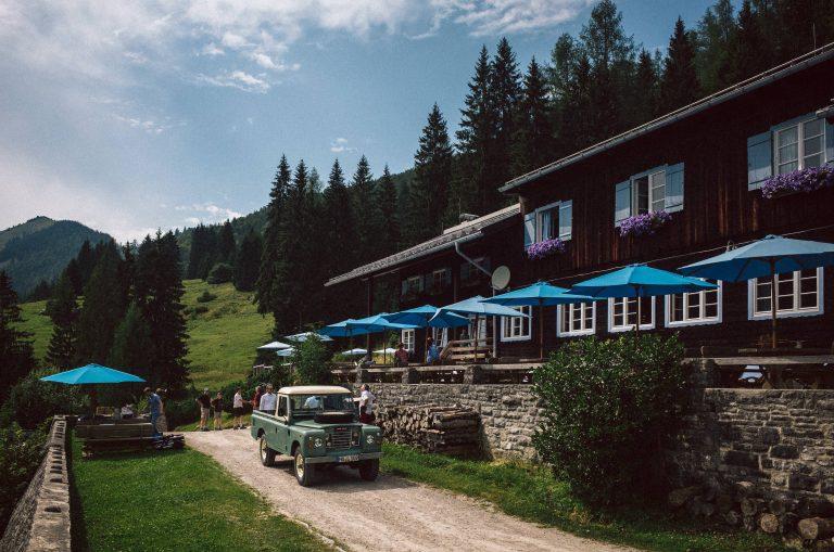 Sommerstimmung im Almbad Sillberghaus mit himmelblauen Sonnenschirmen
