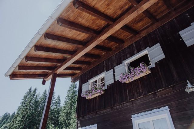 Das Almbad Sillberghaus mit himmelblauen Fensterläden und Blumenbepflanzung