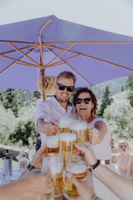 Prost! Feierstimmung im Almbad Sillberghaus - Gäste stoßen unter himmelblauem Sonnenschirm an!